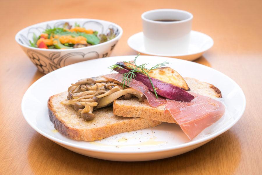 ランチのメインは北欧風オープンサンド。写真は、レモン風味のき のこと生ハムの旨みが口に広がる「3種のきのこと生ハムのオー プンサンド」。旬の県産野菜を使った日替わりのサラダも人気。